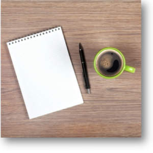 notepad, pen and a cup of coffee on a desktop