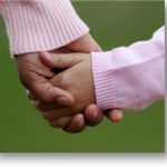 woman holds childs hand