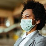 Woman in business suit with face mask